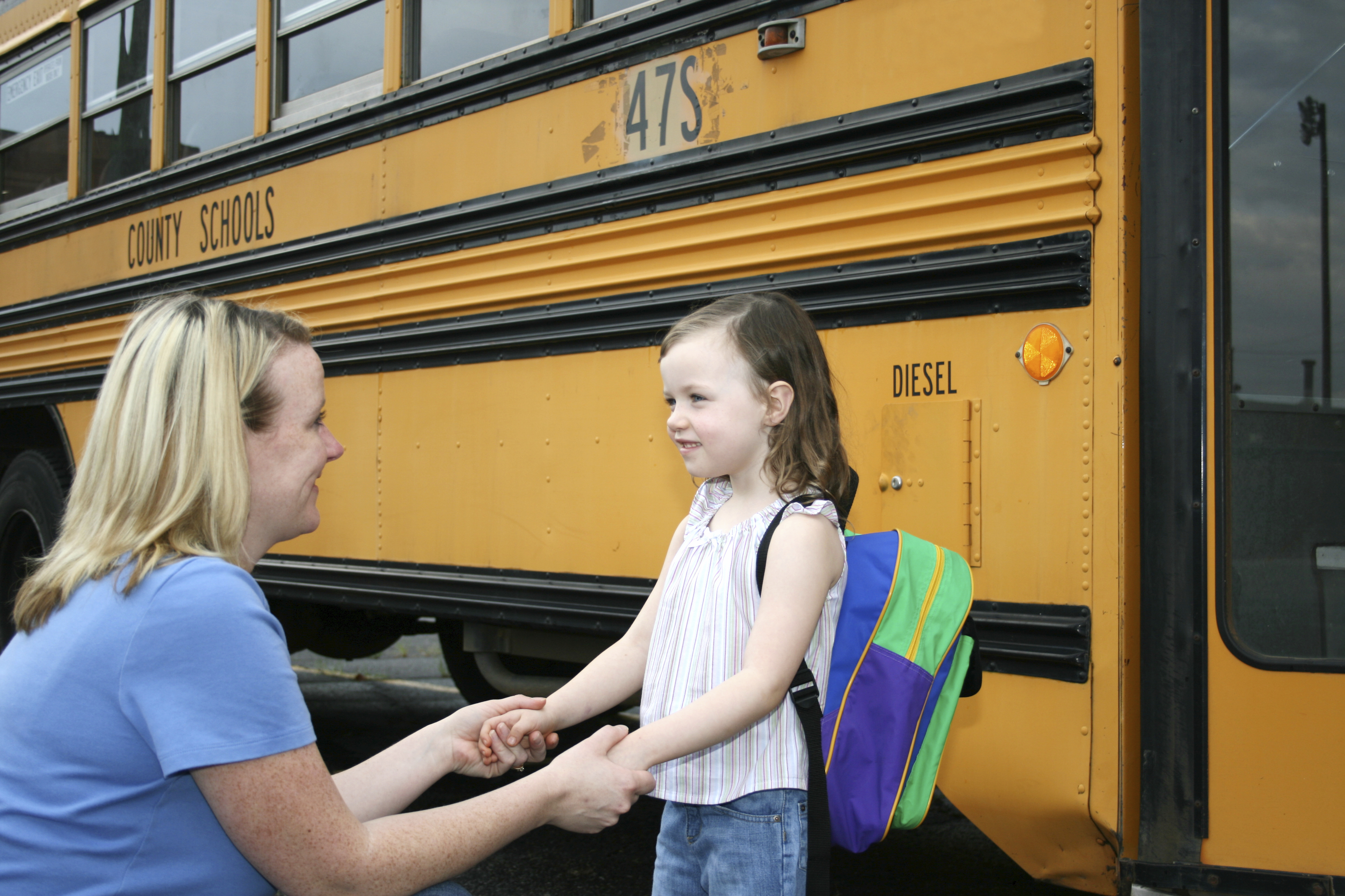 A mother and child at a school bus
